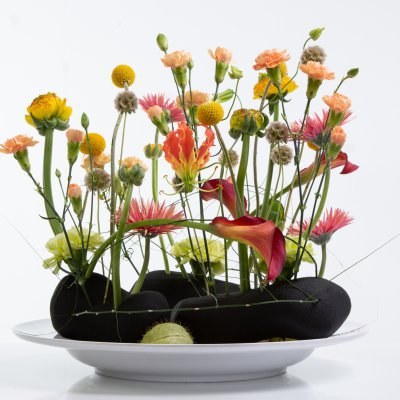 Summery flower arrangement in black floral foam